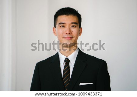 Portrait head shot of a handsome, confident and young Asian man smiling at the camera. He is in a dark suit, white shirt, professional tie and pocket square.  #1009433371