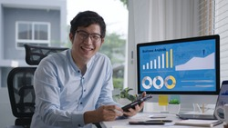 Portrait head shot of young attractive asian man sitting smiling work multiple screen computer and smart tablet on table desk at home in concept freelance data analyst, data scientist for business.