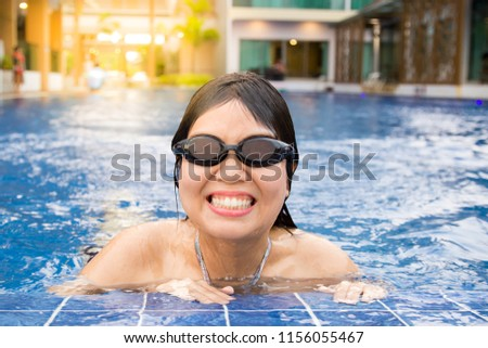 Portrait healthy funny young girl swimmer wearing swim goggles smiling, Enjoy and happy at swimming pool with resort background. Show concept of active lifestyle, Relaxation, Water sport, Recreation. #1156055467