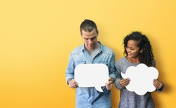 Portrait Hipster African American male and female in casual standing holding and looking at white blank speech bubble over isolated yellow background. Happy Diversity couple holding with smiling face