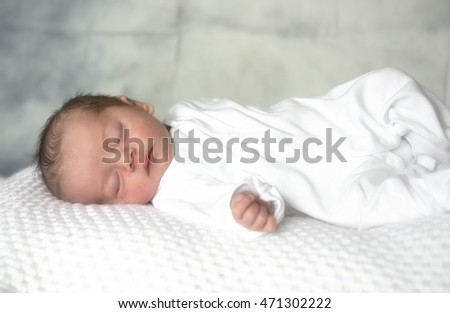 Portrait image of a new born baby boy, laying on a white blanket.  #471302222