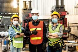 Portrait images of Engineers, Technicians Asian women and men wearing medical masks To prevent dust PM 2.5 And the spread of viruses such as coronavirus of COVID-19, at industrial factory