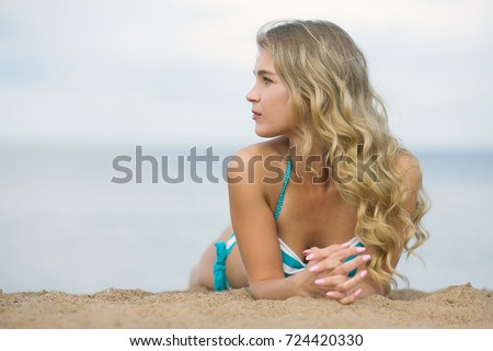 Portrait in profile of a young beautiful blonde with flowing hair on the beach. A gorgeous Caucasian female lies on the beach and enjoys a sunny afternoon and the sound of waves.