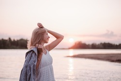 Portrait in profile of a young woman on the beach. A beautiful blonde in a white summer dress stands on the river bank and holds a denim jacket in her hand against the background of sunset and water.