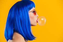 Portrait in profile of glamorous young woman wearing blue wig and sunglasses blowing bubble gum isolated over yellow background