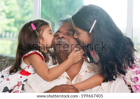 Portrait Indian family at home. Grandchildren kissing on grandparent face. Asian people living lifestyle.