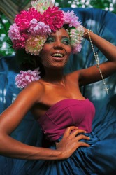portrait laughing African woman in bright clothes , in a pink- blue  dress in flowers hat