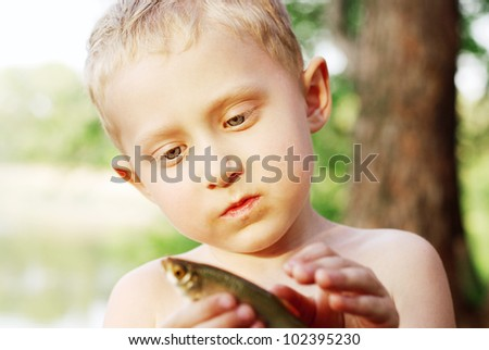 Portrait little boy with fish caught