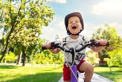Portrait little cute adorable caucasian toddler boy in safety helmet enjoy having fun riding exercise bike in city park road yard garden forest. Child first bike. Kid outdoors sport summer activities
