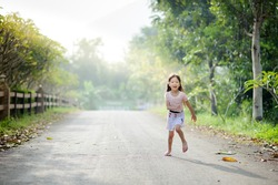 Portrait little cute Asian girl running under the tree on the old road in the morning with sunshine