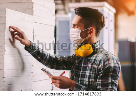 Portrait male foreman inspector in medical face mask and protective headphones checking woodwork stock at factory storage. Man supervisor counting wood inventory. Warehouse worker. COVID-19 quarantine