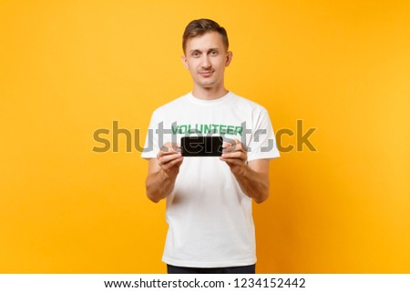 Portrait man in white t-shirt written inscription green title volunteer hold mobile phone blank empty screen isolated on yellow background. Voluntary free assistance help, charity grace work concept