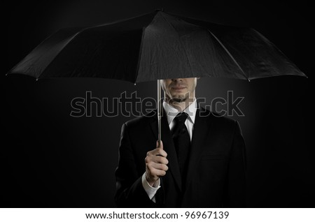 portrait  man the  beautiful  man in black costume with blak umbrella,  special-service agent or  body guard