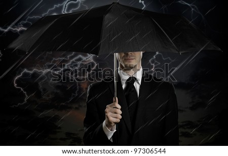 portrait  man the  beautiful  man in black costume with blak umbrella,  special-service agent or  body guard - stock photo