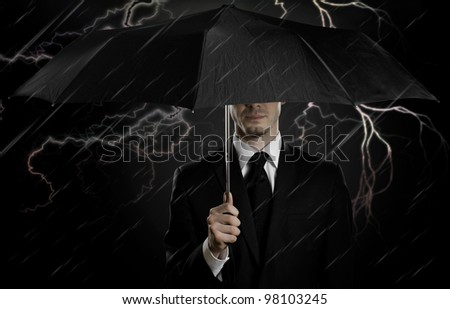portrait  man the  beautiful  man in black costume with blak umbrella,  special-service agent or  guard