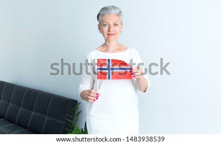 Portrait mature Scandinavian woman holding a flag of Norway.