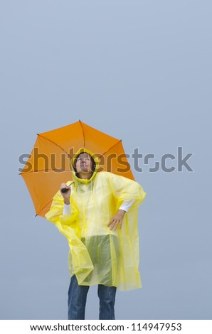 Portrait mature woman standing in the rain, wearing yellow raincoat and orange umbrella, isolated with grey sky as background and copy space.