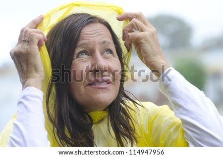 Portrait mature woman standing in the rain, wearing yellow raincoat, isolated with blurred background and copy space.