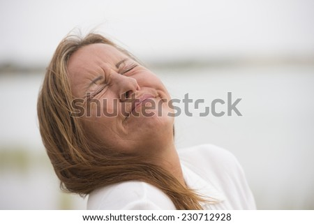Portrait mature woman with sad, stressed, painful facial expression, crying with closed eyes outdoor, blurred background and copy space.