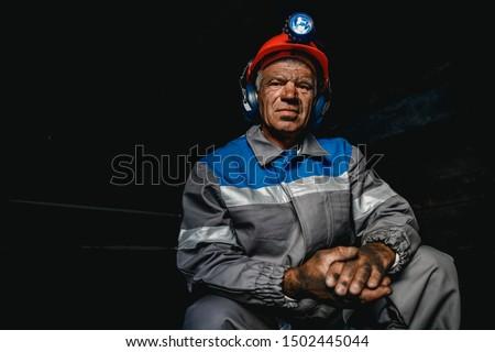 Portrait miner coal man in helmet with lantern in underground mine. Concept industrial engineer. Stock photo ©