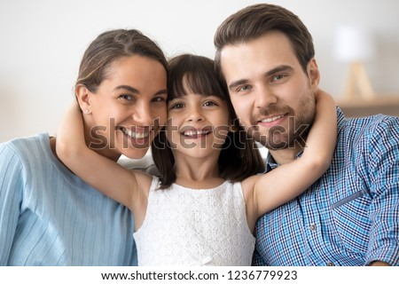 Portrait multi-ethnic beautiful mother father and adorable little preschool daughter sitting together posing smiling looking at camera. New parents for adopted child or happy wellbeing family concept