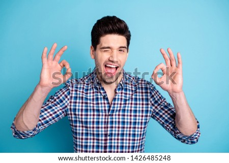 Portrait nice pretty charming youth stubble confident charming excited rejoice amazed funny funky advise decide choose adverts suggest tip news sale checkered modern clothing isolated blue background