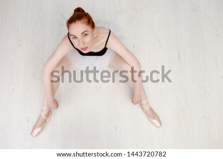 Portrait nice redheaded ballerina sits on the white wood floor She wears a light dance wear and a peach tutu. Top view photo. Horizontal. Copy space #1443720782