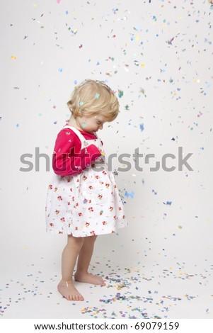 Portrait od cute girl with colorful confetti having fun