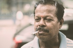 Portrait of a A mid adult senior mature man of Asian and Indian Ethnicity is smoking cigarette. Front View. Close up. Photography taken on 31 May 2019 on World No Tobacco or anti Tobacco Day.