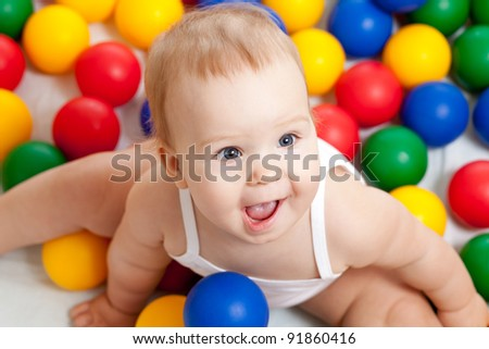 Portrait of a adorable infant sitting among colorful balls