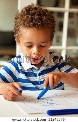 Portrait of a adorable little boy drawing something on paper