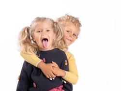 Portrait of a 4-and 3-year-old brother and sister. A boy and a girl embrace, the girl shows her tongue. Beautiful European children on a white background, close-up. Children are curly-haired and blond