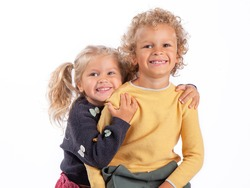 Portrait of a 4-and 3-year-old brother and sister. Beautiful European children on a white background, close-up. A boy and a girl hug and laugh. The children are tanned and curly-haired.