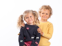 Portrait of a 4-and 3-year-old brother and sister. Boy and girl hug, smile. Beautiful European children on a white background, close-up. The children are curly, tanned, and blond.