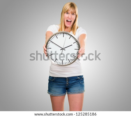 Portrait Of A Angry Woman Holding Clock against a grey background