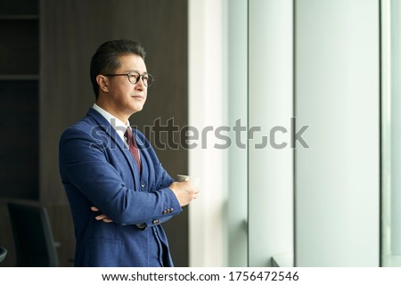 portrait of a asian business leader senior manager standing by window thinking