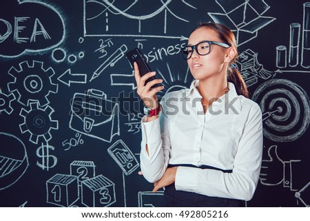 Portrait of a asian business woman in glasses on dark background with pictures  phone in hand #492805216