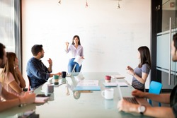 Portrait of a attractive latin woman giving a presentation to coworkers on a white board in a meeting room