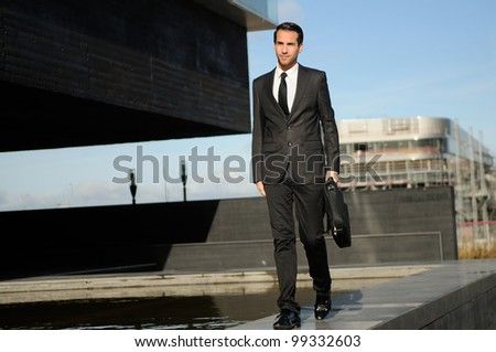 Portrait of a attractive young business man walking in the street with a briefcase