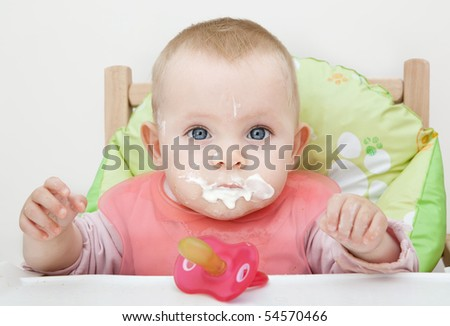 Portrait of a baby eating with a stained face. - stock photo
