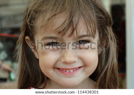 Portrait of a baby girl who smiles a toothy smile with a sparkle of happiness in her eyes.