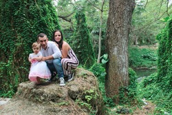 Portrait of a baby girl with her parents. A little girl plays in a natural park with her parents. Place of capture: Havana, Cuba.