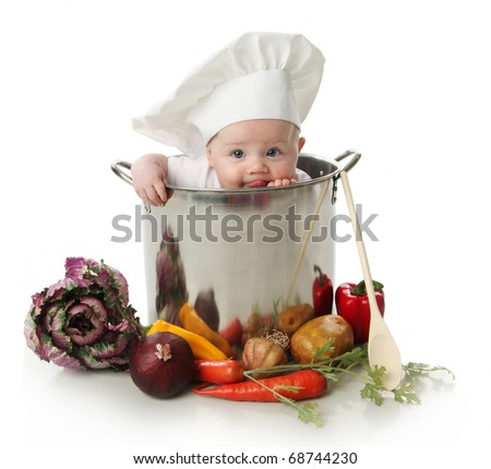 Stock Photo Portrait of a baby sitting wearing a chef hat sitting inside and licking a large cooking stock pot surrounded by vegetables and food, isolated on white