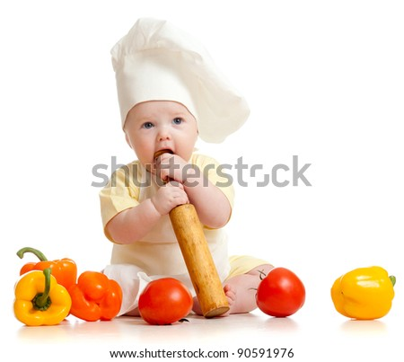 Portrait of a baby wearing a chef hat with healthy  food vegetables, isolated on white