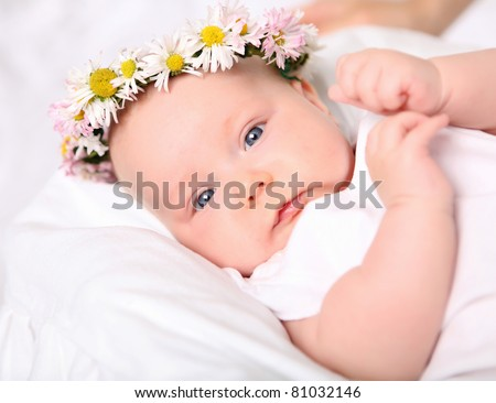 Portrait of a baby with a wreath of flowers on her head.