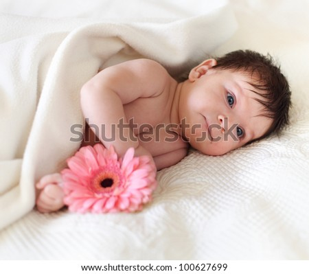 Portrait of a baby with flower lying on the bed. One month old