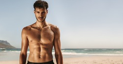 Portrait of a bare chested man with sweat all over the body during workout at a beach. Athletic man doing fitness workout at a beach.