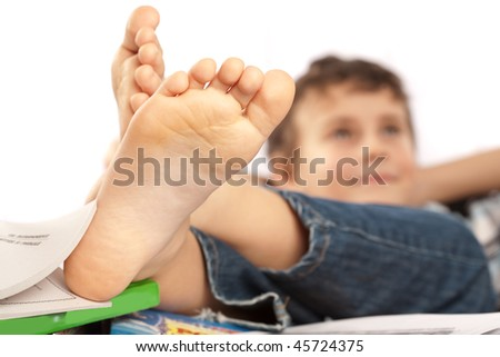 Portrait of a barefoot schoolboy with his feet up on his desk waiting