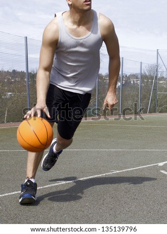 Portrait of a Basketball Player dribbling the ball