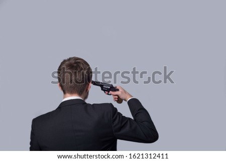 Portrait of a bearded man in a business suit, standing with his back, holding a revolver in his hand, aiming at himself. On a gray background. Criminal type man, gangster, killer, businessman killer